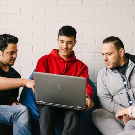 neljä opiskelijaa työskentelee saman kannettavan tietokoneen ympärillä