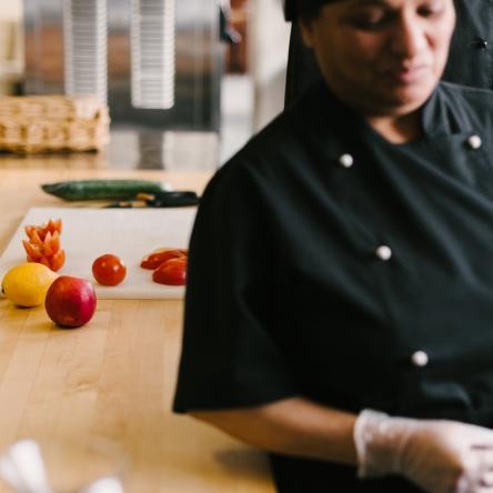 opiskelija keittiössä kokinvaatteissa, taustalla hedelmiä ja leikkuulauta pöydällä